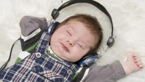 Un bébé avec un casque audio dans un lit