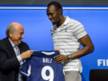 Sepp Blatter, le président de la Fifa, offre un maillot à Usain Bolt lors de sa visite au siège de Zurich le 28 août 2013.